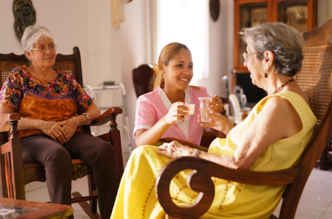 elder woman on a rocking chair with caregiver giving meds