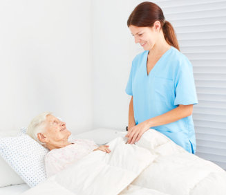 caregiver assisting elder woman to bed
