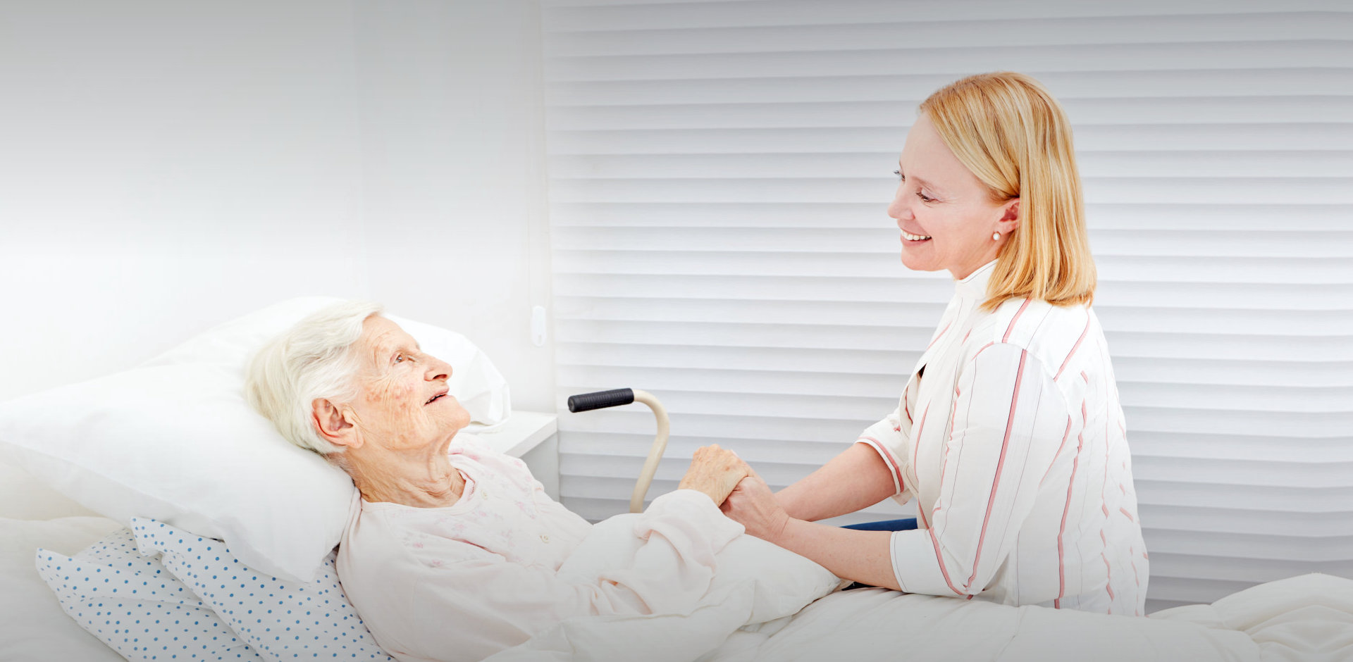 elder woman in bed with caregiver
