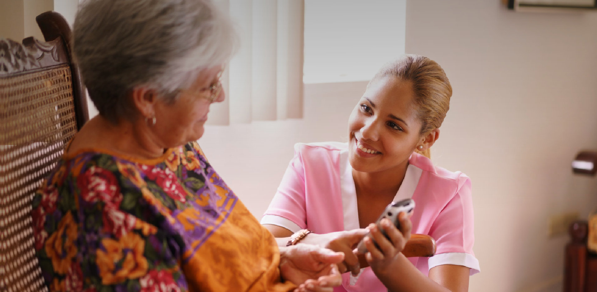 caregiver showing to elder woman an article on her phone